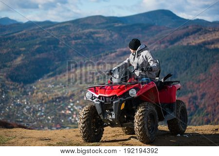Man In Winter Clothes On A Red Quad Bike On A Mountain Top Enjoying The View Of The Mighty Mountains