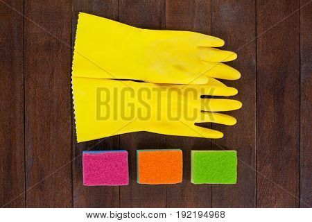 Close-up of glove and scrubber arranged on wooden floor