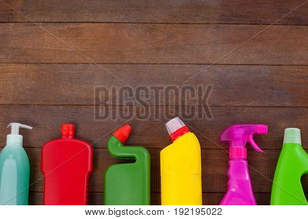 Various detergent bottles arranged on a wooden floor