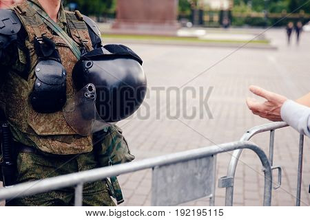 woman stretches out her hand to the military man with a helmet and uniform. Concept military situation and rallies in Moscow, Russia.