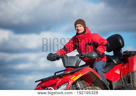 Close-up Portrait Of Man In A Red Winter Clothes Riding On Red Quad Bike In The Mountains Top. Blue