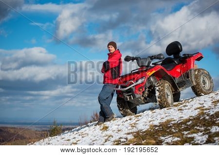 Guy In A Red Winter Clothes Standing Near Red Atv Quad Bike, Looking To The Camera On Snowy Mountain