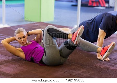 fitness, sport, training, exercising and people concept - woman and man doing curl ups and push ups in gym