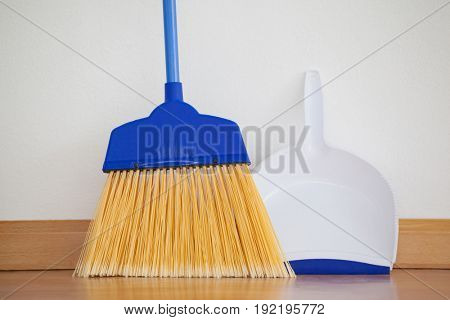 Close-up of dustpan and sweeping broom leaning against white wall