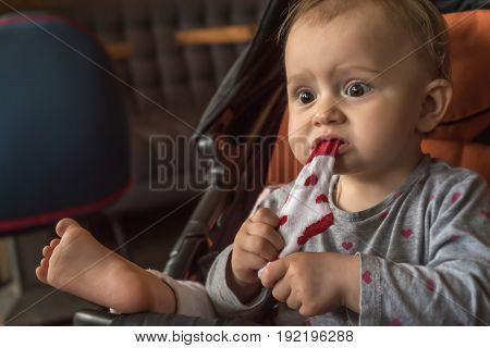 Very expressive and emotional girl watching tv with eyes wide open and eats her sock