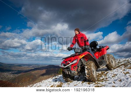 Bottom View Of A Man On The Sports Atv Quadbike At The Snow-covered Hill Against The Blue Cloudy Sky