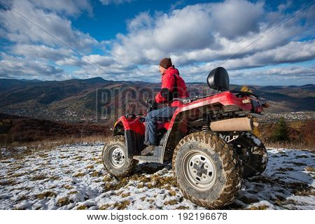 Sports Atv Quad Bike With Rider At The Snow-covered Slope Against The Blue Cloudy Sky, Mountains And