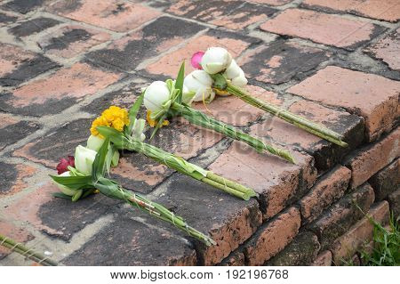 white lotus on other flower on cement floor for respect buddha statue in Ayutthaya , Thailand