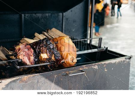 Big juicy pork roast cooking on open fire outdoors