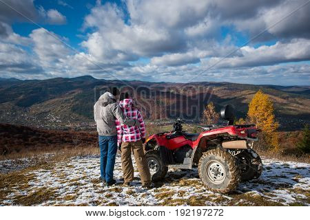 Rear View Of A Guy Hugging A Girl Near The Atv On A Mountain Top Under The Blue Sky With Cumulus Clo