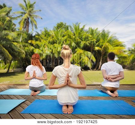 fitness, sport, yoga and healthy lifestyle concept - group of people exercising in reverse prayer pose over natural exotic background with palm trees
