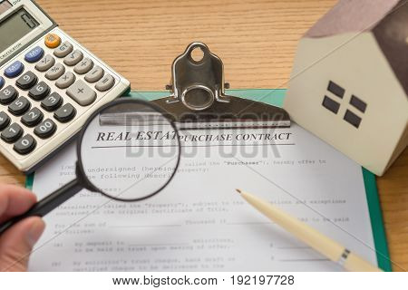 real estate purchase contact with an architectural model and a calculator with some part highlighted