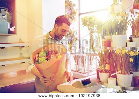 people, sale, retail, business and floristry concept - happy smiling florist man with bunch counting cost at flower shop cashbox