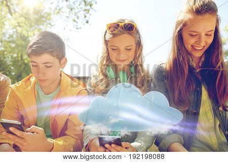 technology, cloud computing and people concept - group of happy teenage friends with smartphone and headphones outdoors