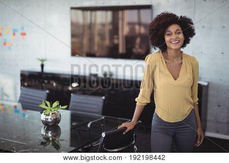 Portrait of smiling businesswoman standing in meeting room