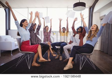 Cheerful business people throwing papers while sitting in creative office