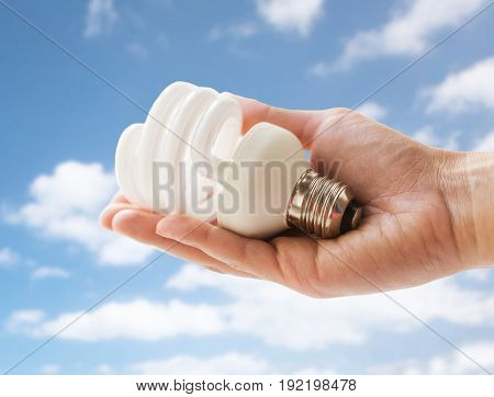 recycling, electricity and ecology concept - close up of hand holding energy saving lightbulb or lamp over blue sky and clouds background