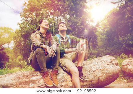 travel, hiking, backpacking, tourism and people concept - smiling couple with backpacks resting and enjoying sun in nature