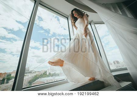 Beautiful stylish bride walks on the windowsill