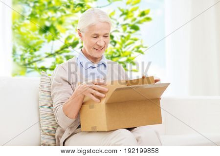 age, delivery, mail, shipping and people concept - happy smiling senior woman looking into open parcel box at home over green natural background