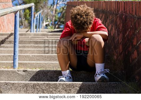 Upset boy sitting on staircase in the boot camp on a sunny day