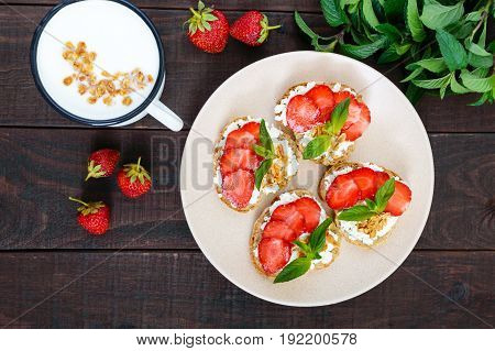 Mini sandwiches with cottage cheese fresh strawberries decorated with mint leaves on rye bread and a mug of yogurt on a dark wooden background. Top view. Proper nutrition. Healthy food. Dietary menu.