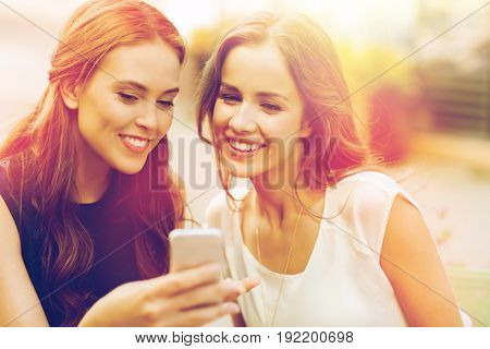 technology, lifestyle, friendship and people concept - happy young women or teenage girls with smartphone at outdoor cafe