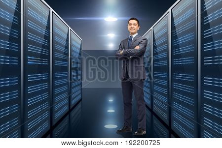 business, people and technology concept - smiling businessman in suit over server room background