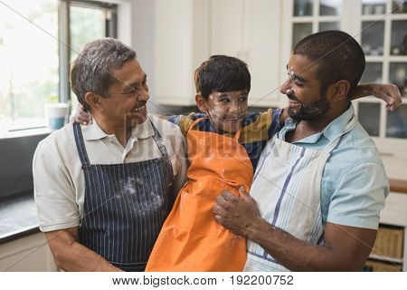 Happy multi-generation family standing together in kitchen at home