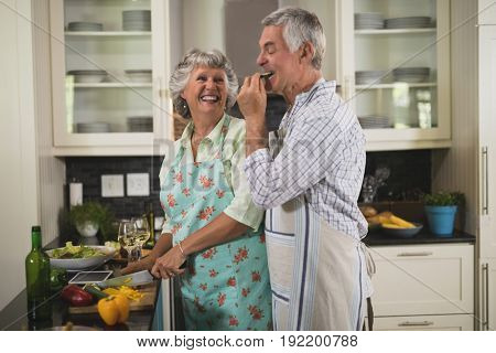 Playful senior couple enjoying while cooking in kitchen at home