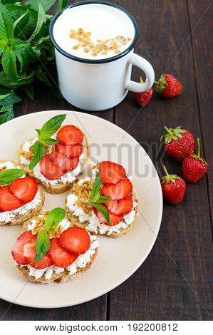 Mini sandwiches with cottage cheese fresh strawberries decorated with mint leaves on rye bread and a mug of yogurt on a dark wooden background. Proper nutrition. Healthy food. Dietary menu
