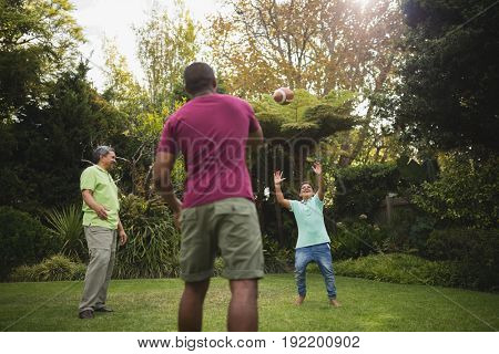 Multi generation family playing with rugby ball at park