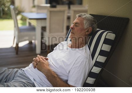 Senior man resting on lounge chair at porch