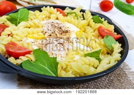 Fusilli pasta fried eggs and tomatoes. Serve on a cast-iron frying pan on a white wooden background. Close up