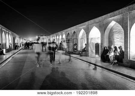 ISFAHAN IRAN - OCTOBER 21 2016 : Unidentified Iranian people walk and sit on Si-o-seh pol or Allahverdi Khan Bridge at night the bridge of 33 arches in Isfahan Iran.