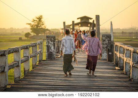 Unidentified couple Burmese woman walk on U Bein Bridge at sunset the oldest and longest teak bridge (Wooden footbridge) in the world at Amarapura township near Mandalay Myanmar