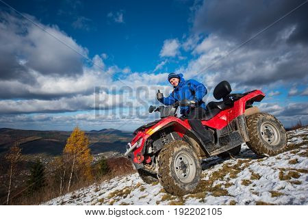 Happy Male Rider Driving On Atv Off-road Vehicle In A Mountains And Showing Thumb Up Gesture Of Good