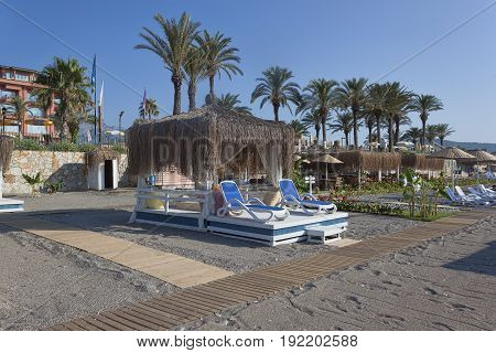 Place On The Beach With Sun Beds And A Gazebo With A Thatched Roof