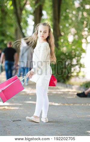 shopping concept. cute little girl walking with the pink shopping bags