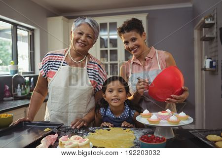Portrait of happy family preparing desserts in kitchen at home