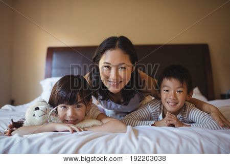 Portrait of mother with daughter and son relaxing on bed in bed room at home