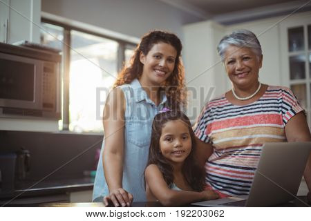 Portrait of happy family using laptop in kitchen at home