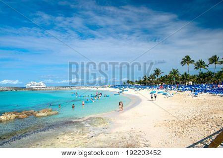 Great stirrup cay Bahamas - January 8 2016: people resting on beach on white sand with turquoise sea or ocean and lounge chairs on sunny day on blue sky. Summer vacation. Tropical resort. Paradise
