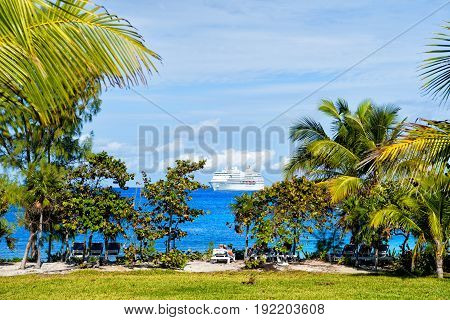 palm trees green grass lounge chairs and white cruise ship on beach in turquoise sea or ocean water on sunny day on blue sky background. Summer vacation. Luxury resort. Tropical paradise