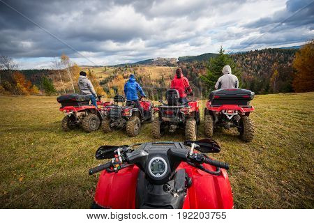 View From Quad Bike. Four Men At Atv Enjoying Beautiful Landscape Of Rolling Countryside And Colorfu