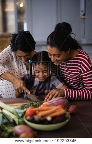 Smiling multi-generation family preparing food together in kitchen at home