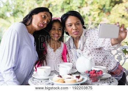 Multi-generation family taking selfie while sitting together by breakfast table at home