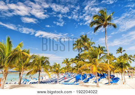 Great stirrup cay Bahamas - January 8 2016: green palm trees on white sand beach with lounge chairs people and turquoise sea or ocean on sunny day on blue sky. Summer vacation resort. Paradise