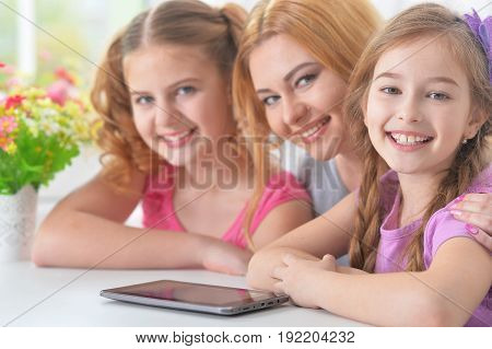Portrait of a mother with daughters reading book