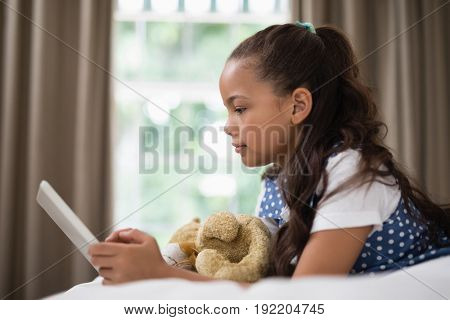 Side view of smiling girl using digital tablet while lying on bed at home